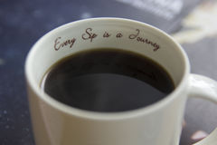 Cup of freshly brewed black coffee. Focus at text printed on the cup Royalty Free Stock Photography