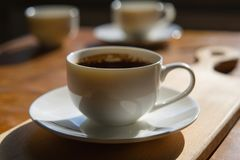 Cup of freshly brewed coffee on a blurry background of two cups. Wooden table in the room Royalty Free Stock Image