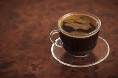 A Cup of freshly brewed coffee on a brown table. Royalty Free Stock Photography