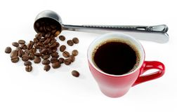 A cup of freshly brewed coffee with foam against the background of a blurry measuring spoon with coffee beans. Isolated on white royalty free stock images