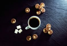 Cup of freshly brewed coffee and milk chocolate candies. Cup of freshly brewed coffee, milk chocolate candies and sugar on black stone tray. Sweet breakfast or Stock Images