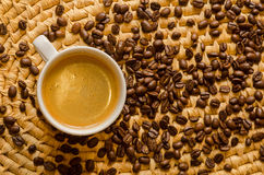 Cup with freshly brewed espresso and coffee beans on a tray. Cup with freshly made coffee and roasted espresso beans on a woven serving tray Stock Image