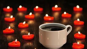 Cup of freshly brewed and fragrant coffee by romantic candlelight. Cup of freshly brewed and fragrant coffee, lot of candles in the shape of heart, brown wooden stock video