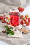 A cup of freshly brewed strawberry tea with fresh mint. Stock Photos