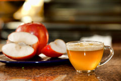 Cup of freshly juiced apple on kitchen counter next to plate of raw apples Royalty Free Stock Images