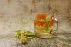 A cup of freshly linden tea. White vase with a bouquet of fragrant yellow flowers and leaves of linden and dried grass hedgehogs. Latin D?ctylis glomer?ta stock image