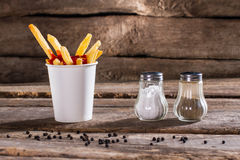 Cup of fries with pepperbox. Royalty Free Stock Photos