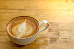 Cup of frothy cappucino on a wooden table with lots of room for. Copyspace.  This yummy and delicious creamy drink is part of your morning routine and helps you Stock Photography