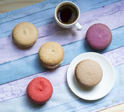Cup of frothy espresso coffee with colourful French macaroons. White cup of frothy espresso coffee with colourful French macaroons on blue background Stock Images