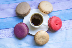 Cup of frothy espresso coffee with colourful French macaroons. White cup of frothy espresso coffee with colourful French macaroons on a blue background Stock Photos