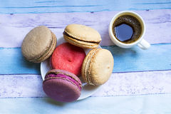 Cup of frothy espresso coffee with colourful French macaroons. White cup of frothy espresso coffee with colourful French macaroons on blue background Royalty Free Stock Image