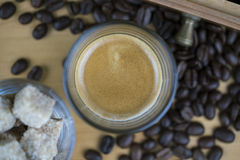 Cup of frothy hot coffee with beans and sugar Stock Photography