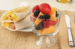 Cup of fruit and breakfast burritos Stock Images