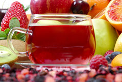 Cup of fruit tea. Cup of tea in front of fresh fruits Stock Photography