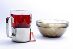 Cup of fruit tea. And a pot with sugar cubes royalty free stock photography