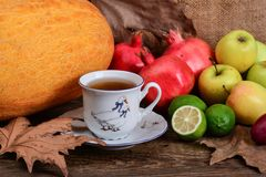 Cup of fruit tea and autumn colorful fruits Royalty Free Stock Photo