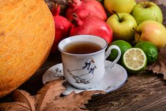 Cup of fruit tea and autumn colorful fruits Royalty Free Stock Photography