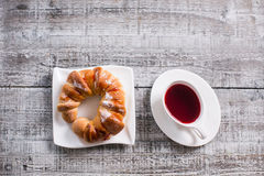 Cup of fruit tea with croissant Royalty Free Stock Photos