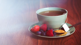 Cup of fruit tea with strawberries, raspberries and blueberries on wooden table, with copy space. Stock Photography