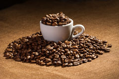 Cup full of black coffee beans Royalty Free Stock Images