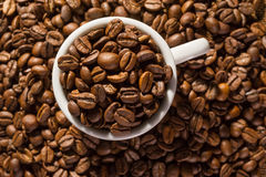 Cup full of black coffee beans Royalty Free Stock Photos