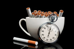 Cup full of cigarettes and stopwatch Royalty Free Stock Images