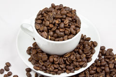 Cup Full Of Coffee. A cup and saucer overflowing with coffee beans royalty free stock photos
