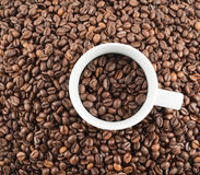 Cup full of coffee beans. Cup full of coffee bean over covered with beans flat surface as abstract background Royalty Free Stock Photos