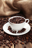 Cup full of coffee beans on brown wooden background Royalty Free Stock Images