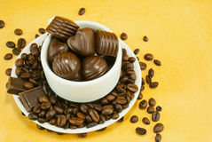 Cup full with coffee beans and chocolate candies Royalty Free Stock Photography
