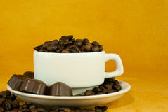 Cup full with coffee beans and chocolate candies Royalty Free Stock Images