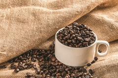 Cup full of coffee beans on the cloth sack.  Royalty Free Stock Photos