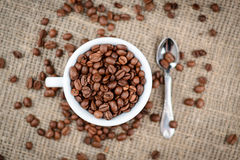 Cup full of coffee beans on the cloth sack background.  Stock Images