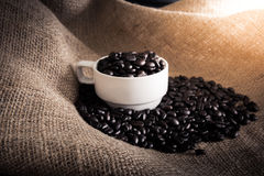Cup full of coffee beans on the cloth sack Royalty Free Stock Photography