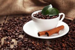 Cup full of coffee beans with leaves and cinnamon on brown wooden background Stock Photos