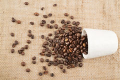 Cup full of coffee beans over hessian cloth Royalty Free Stock Photography
