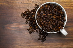 Cup full of coffee beans over wooden background Stock Photo