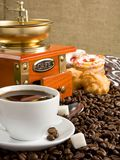 Cup full of coffee, beans, pot and grinder Stock Image