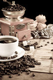 Cup full of coffee, beans, pot and grinder Royalty Free Stock Photo