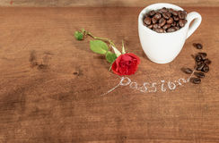 A cup  full of coffee beans with red rose. Stock Photography