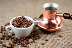 Cup full of coffee beans with turkish cezve on the cloth sack background.  Royalty Free Stock Photos