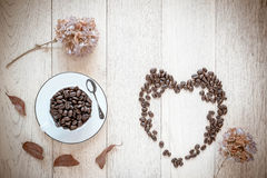 Cup full of coffee beans on wooden background. Coffee in love. Stock Images