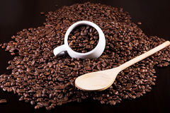 Cup full of coffee beans and a wooden spoon. On a dark background. Concept Stock Photo