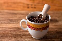 Cup full of coffee grains and wooden spoon. Photo of Cup full of coffee grains and wooden spoon inside placed on old wooden board Stock Photo