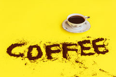 A cup full of coffee. Ready to drink with the word coffee drawn with coffee grounds Royalty Free Stock Photography