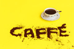 A cup full of coffee with the words made of coffee powder. A cup full of coffee ready to drink with the word coffee drawn with coffee grounds Royalty Free Stock Photography