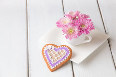 Cup full of pink  mum flowers and  heart shape cookie on white w Stock Images