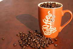 Cup full of roasted coffee beans on wooden background. Stock Photography