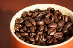 Cup full of roasted coffee beans on wooden background. Royalty Free Stock Image