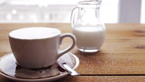 Cup full of spilled coffee and sugar on table. Unhealthy eating, diabetes, object and drinks concept - cup full of spilled coffee and sugar on wooden table with stock footage